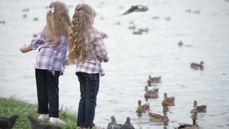Two-Little-Girls-At-Lake-Feeding-Ducks-Bread
