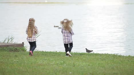 Two-Little-Girls-At-Park-Running-To-Water-And-Feeding-Ducks