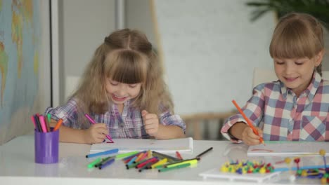 Two-Little-Girls-Drawing-With-Colored-Pencils-At-Drawing-Class-And-Smiling