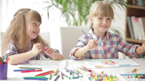 Two-Little-Girls-Sitting-At-Desk-Drawing-With-Colored-Pencils-And-Laughing