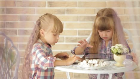Two-Little-Girls-Sitting-At-Table-At-Cafe-And-Using-Touchpads