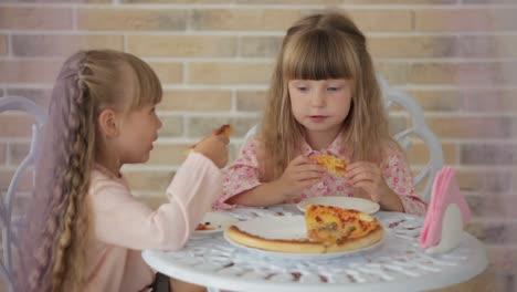 Dos-Niñas-Sentadas-A-La-Mesa-En-El-Café-Comiendo-Pizza-Y-Sonriendo