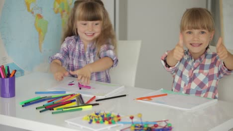 Two-Little-Girls-Sitting-At-Table-Drawing-With-Colored-Pencils