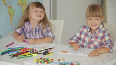 Two-Little-Girls-Sitting-At-Table-Drawing-With-Colored-Pencils-And-Smiling