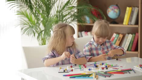 Two-Little-Girls-Sitting-At-Table-Playing-With-Logic-Toys-And-Smiling-At-Camera