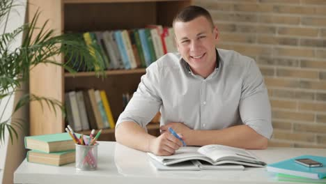 Estudiante-Universitario-Sentado-A-La-Mesa-Rodeado-De-Libros-Y-Escribiendo-En-El-Cuaderno
