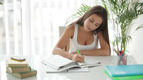Young-Girl-Sitting-At-Table-And-Writing-In-Notebook-With-Smile