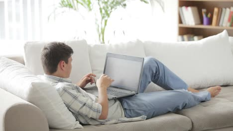 Young-Man-Lying-On-Sofa-Working-On-Laptop-Looking-At-Camera-And-Smiling
