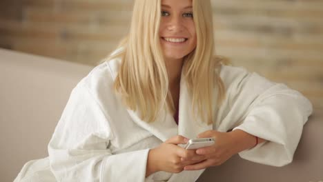 Young-Woman-In-Bathrobe-Relaxing-On-Sofa-Using-Cellphone-Looking-At-Camera