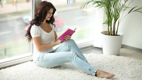 Attractive-Girl-Sitting-By-Window-Reading-Book-Closing-It-And-Smiling-At-Camera