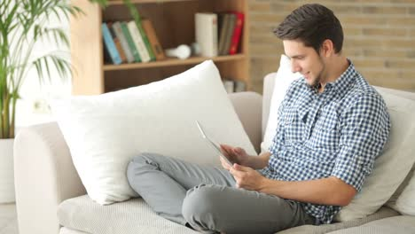 Attractive-Guy-Sitting-On-Sofa-And-Using-Touchpad