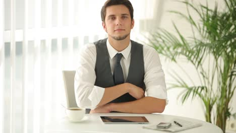 Attractive-Man-Sitting-At-Table-And-Using-Touchpad