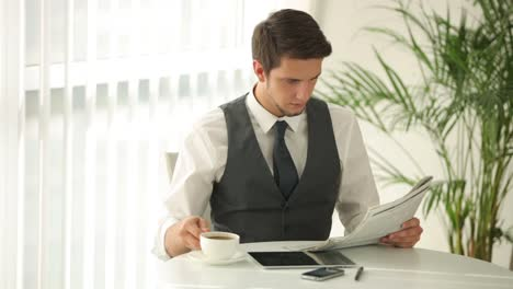 Attractive-Young-Man-Sitting-At-Table-Drinking-Coffee-And-Reading-Newspaper