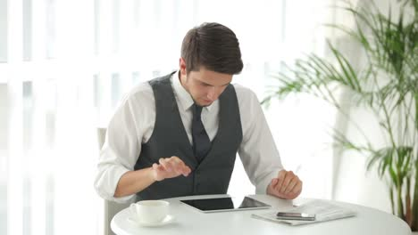 Atractivo-Joven-Sentado-En-La-Mesa-Con-Touchpad-Y-Con-Tarjeta-De-Crédito