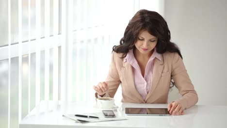 Atractiva-Mujer-Joven-Sentada-En-La-Mesa-De-Oficina-Con-Touchpad-Removiendo-Café