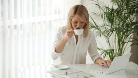Atractiva-Mujer-Joven-Sentada-En-La-Mesa-Usando-Laptop-Tomando-Café-Y-Sonriendo