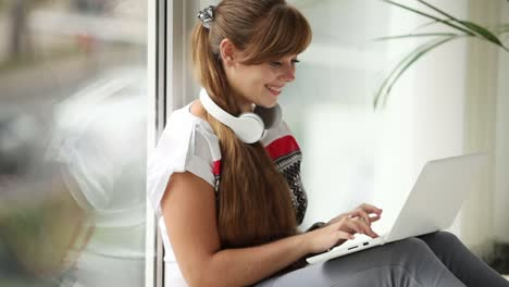 Beautiful-Girl-In-Headset-Sitting-By-Window-Using-Laptop-Looking-At-Camera