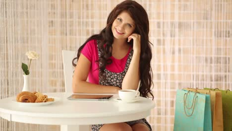 Beautiful-Girl-Sitting-At-Cafe-With-Shopping-Bags-And-Smiling-At-Camera