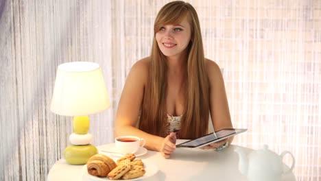 Hermosa-Mujer-Joven-Sentada-En-El-Café-Con-Touchpad-Mirando-A-La-Cámara