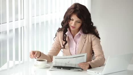 Hermosa-Mujer-Joven-Sentada-En-La-Mesa-Leyendo-El-Periódico-Revolviendo-Café-Y