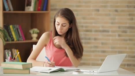 Chica-Estudiante-Aburrida-Sentada-En-El-Escritorio-Y-Escribiendo-En-El-Libro-De-Trabajo