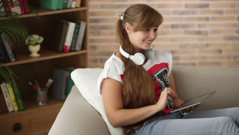 Charming-Girl-In-Headset-Sitting-On-Sofa-Using-Touchpad-Looking-At-Camera