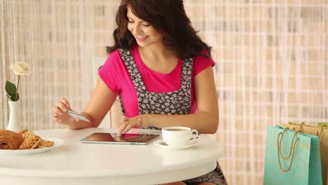 Charming-Girl-Sitting-At-Cafe-With-Shopping-Bags-Holding-Credit-Card-And-Using