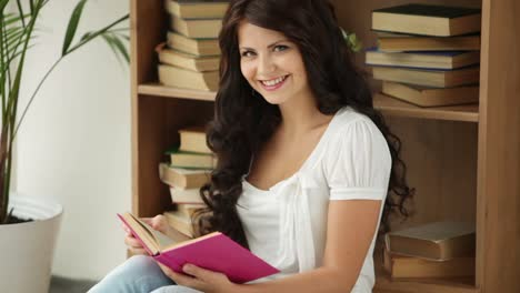 Charming-Girl-Sitting-On-Floor-Reading-Book-Looking-At-Camera-And-Smiling