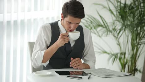 Charming-Man-Sitting-At-Table-Reading-Newspaper-And-Drinking-Coffee