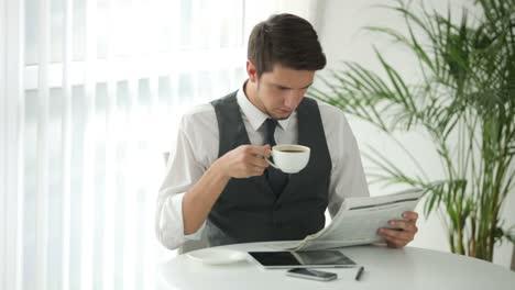 Encantador-Joven-Sentado-En-La-Mesa-Leyendo-El-Periódico-Y-Tomando-Café