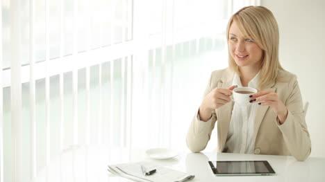 Encantadora-Mujer-Joven-Sentada-En-La-Mesa-Tomando-Café-Y-Sonriendo-A-La-Cámara