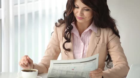 Charming-Young-Woman-Sitting-At-Table-Reading-Newspaper-Stirring-Coffee