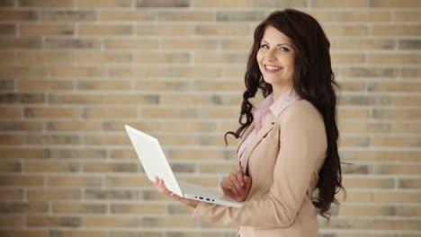 Encantadora-Joven-Usando-Laptop-Mirando-A-Cámara-Y-Sonriendo