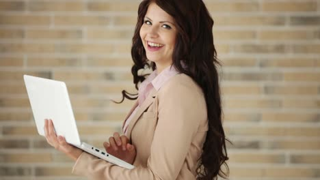 Cheerful-Businesswoman-Using-Laptop-And-Smiling-At-Camera