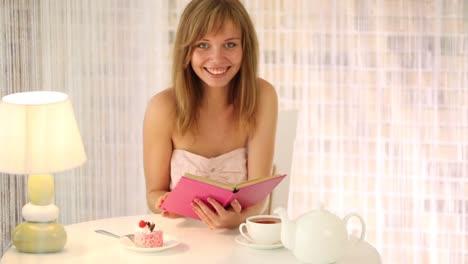 Cheerful-Girl-Sitting-At-Cafe-Reading-Book-Looking-At-Camera-And-Smiling