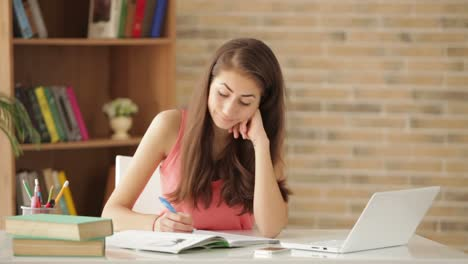 Cheerful-Girl-Sitting-At-Desk-Writing-In-Workbook-Looking-At-Camera-And-Smiling-03