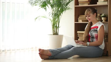 Cheerful-Girl-Sitting-On-Floor-Using-Laptop-Looking-At-Camera-And-Smiling-02