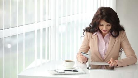 Alegre-Mujer-Joven-Sentada-En-La-Mesa-Con-Touchpad-Con-Tarjeta-De-Crédito