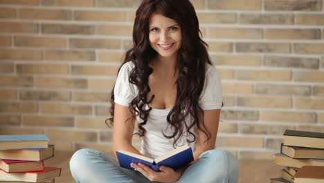 Cute-Brunette-Girl-Sitting-On-Floor-Reading-Book-And-Smiling-At-Camera