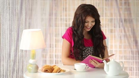 Cute-Girl-Sitting-At-Cafe-Reading-Book-Closing-It-And-Smiling-At-Camera