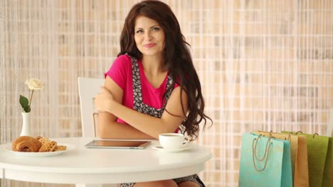 Cute-Girl-Sitting-At-Cafe-With-Shopping-Bags-And-Smiling-At-Camera