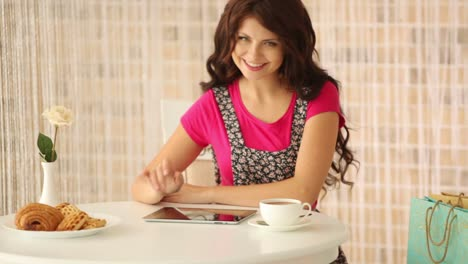 Cute-Girl-Sitting-At-Cafe-With-Shopping-Bags-Using-Touchpad-And-Smiling