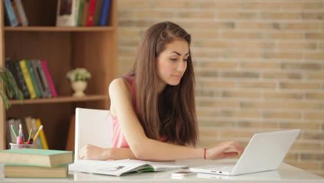 Linda-Chica-Sentada-En-El-Escritorio-Escribiendo-En-El-Libro-De-Trabajo-Usando-La-Computadora-Portátil-Y-Sonriendo