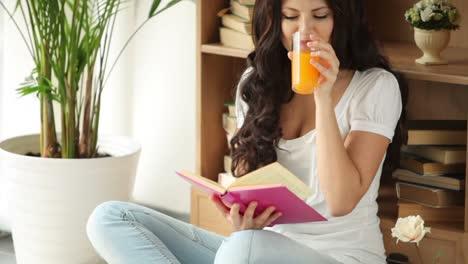 Süßes-Mädchen-Das-Auf-Dem-Boden-Sitzt-Ein-Buch-Liest-Und-Saft-Trinkt