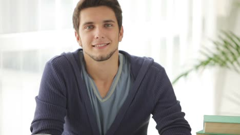 Cute-Guy-Sitting-At-Table-Studying-And-Writing-In-Notebook