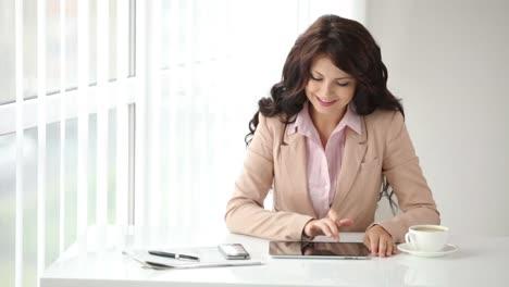 Linda-Mujer-Joven-Sentada-En-La-Mesa-De-Oficina-Con-Touchpad-Y-Teléfono-Celular