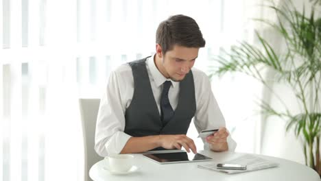 Good-Looking-Guy-Sitting-At-Table-With-Touchpad-And-Holding-Credit-Card