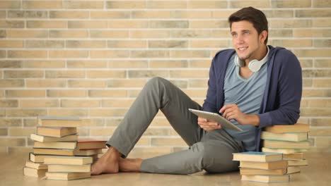 Good-Looking-Guy-Sitting-Of-Floor-With-Books-And-Using-Touchpad