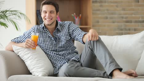 Good-Looking-Guy-Sitting-On-Couch-And-Drinking-Juice