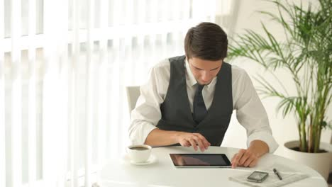 Good-Looking-Man-Sitting-At-Table-And-Using-Touchpad